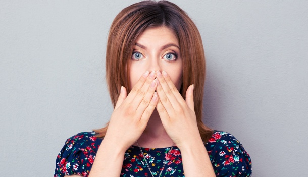 Portrait of a scared woman covering her lips over gray background. Looking at camera